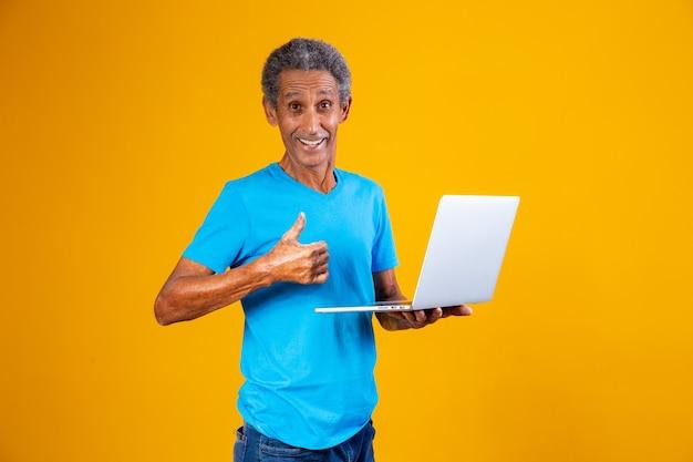 노트북 쇼핑이나 온라인 작업을 하는 노인. 노트북 컴퓨터를 들고 엄지손가락을 가진 노인.