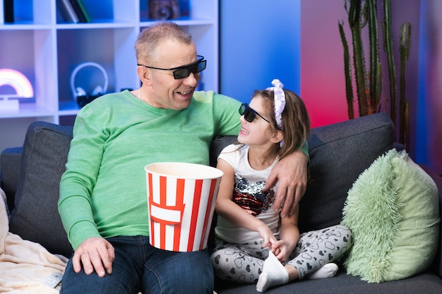 Elderly man with a little girl wearing 3d glasses watching tv andeating popcorn. senior, old generation, grandphather family time relax with young girl kid on sofa in living room concept