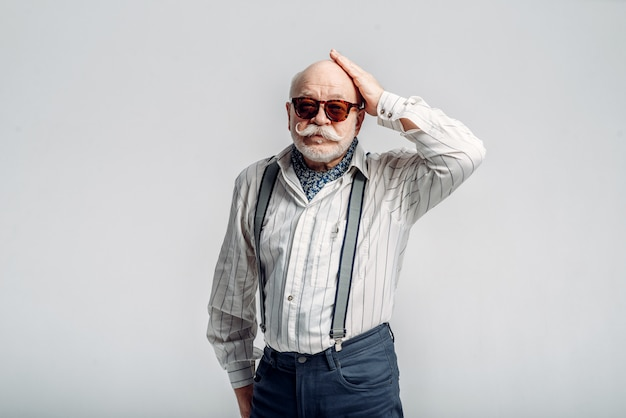 Elderly man with mustache poses in sunglasses