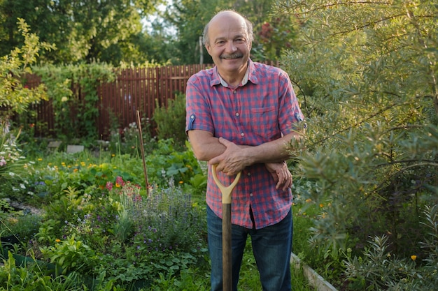 Elderly man with a mustache standing in the summer garden, smiling.