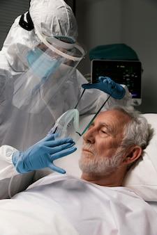 Пожилой мужчина с респиратором на больничной койке