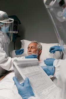 의사 옆에 인공 호흡기를 가진 노인