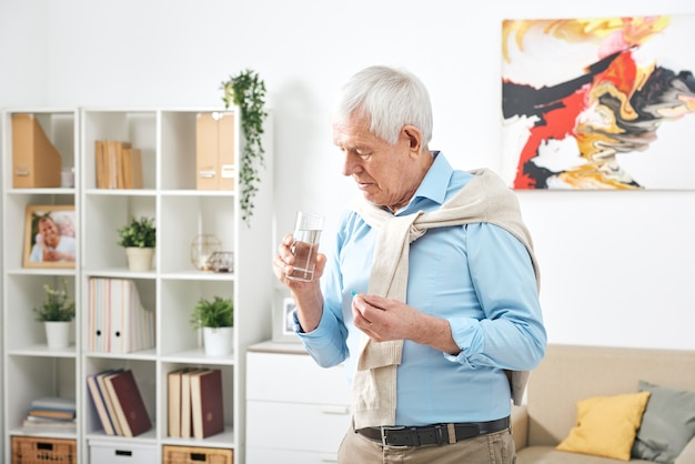 Пожилой мужчина в свитере, обернутом вокруг плеч, принимает таблетки и пьет воду дома