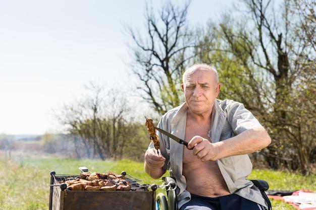 단추를 풀지 않은 셔츠를 입고 휠체어에 앉아 막대기와 칼에 구운 고기를 들고 공원에서 굽고 있는 동안 카메라를 바라보는 노인.