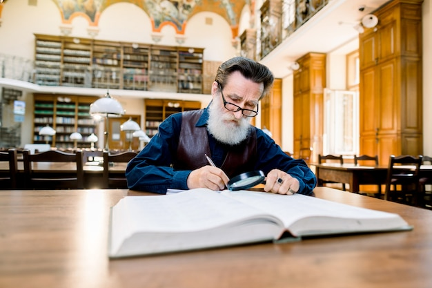 Elderly man with white beard and glasses working in an antique library with books, sitting at the vintage table. education, library concept