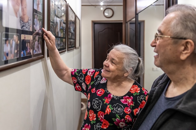 An elderly man and woman are looking at family photographs.