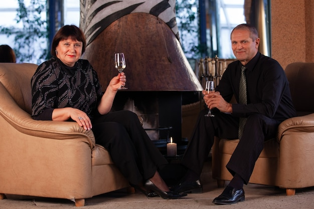 Elderly man and woman drink champagne in a romantic setting.