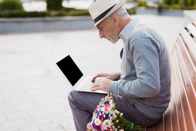 Elderly man work in laptop. old guy sit on bench.