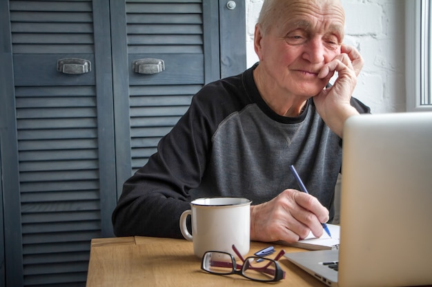 Elderly man working on laptop, count, looking at screen, drinking tea and makes notes in a notebook.