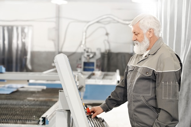 Elderly man working with laser cutting machine on factory.