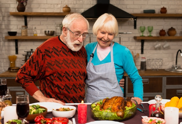 Elderly married couple looking at the cooked turkey