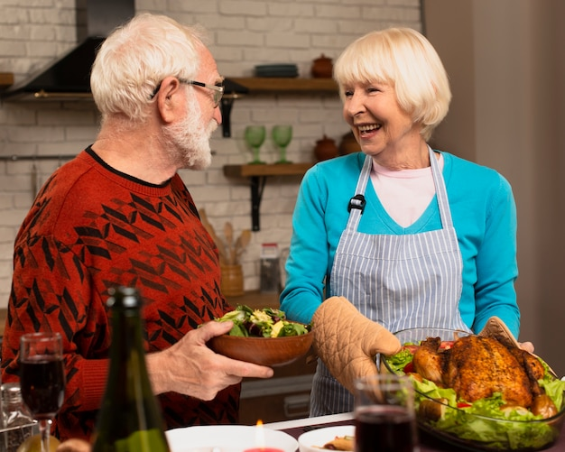 Elderly married couple looking at each other in the kitchen