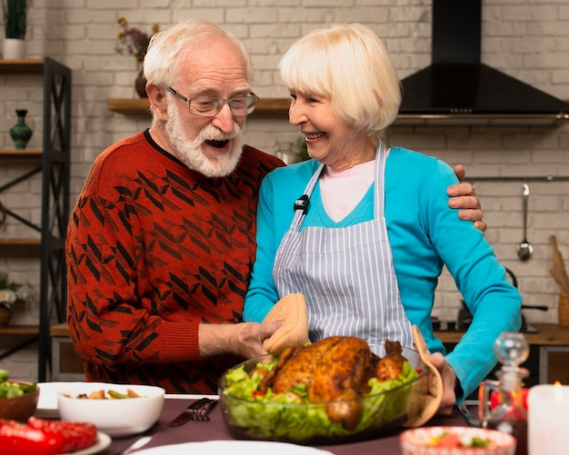 Elderly married couple playing in the kitchen and holding the turkey