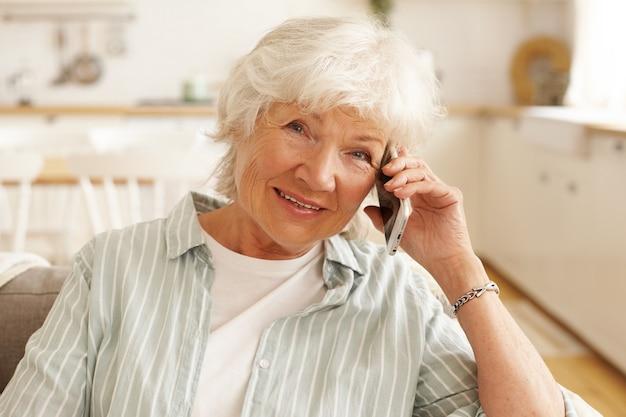 Anziana donna europea matura in camicia a righe avente conversazione telefonica tramite applicazione online utilizzando la connessione internet wireless gratuita ad alta velocità a casa, guardando con un sorriso allegro