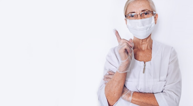 Elderly mature woman doctor or nurse raised finger in a white medical coat, gloves, face mask wearing personal protective equiment isolated. healthcare and medicine concept. covid-19 pandemic crisis