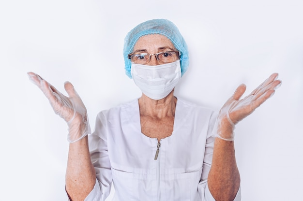 Elderly mature woman doctor or nurse raised hands in a white medical coat, gloves, face mask wearing personal protective equipment isolated. healthcare and medicine concept. covid-19 pandemic