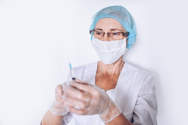 Elderly mature woman doctor or nurse with syringe in a white medical coat, gloves, face mask wearing personal protective equipment isolated. healthcare and medicine concept. covid-19 pandemic crisis