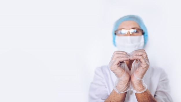 Пожилые зрелые доктор или медсестра женщины показывая сердце подписывают внутри белое медицинское пальто, перчатки, лицевую маску нося изолированные средства индивидуальной защиты. концепция здравоохранения и медицины. covid-19 пандемия