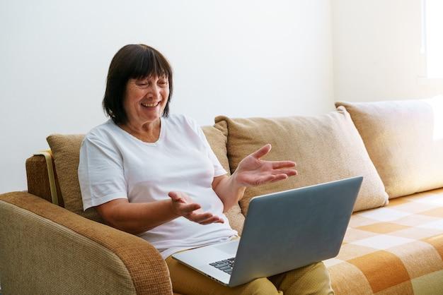 Пожилая зрелая женщина, использующая беспроводные приложения для ноутбука, просматривает интернет, сидя на диване, улыбаясь среднего возраста