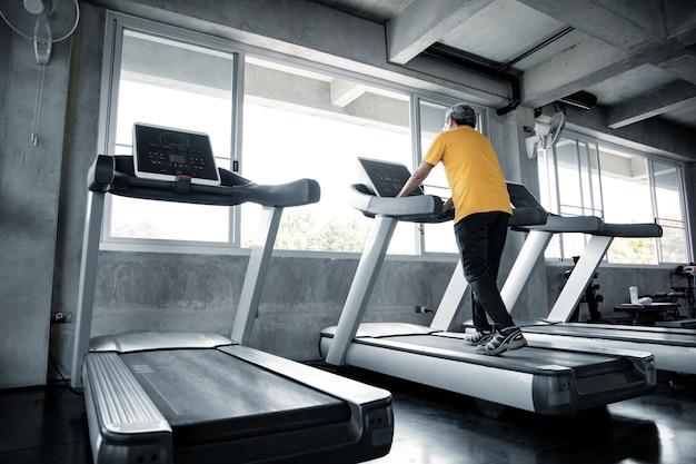 노인 남성은 체육관에서 러닝 머신에서 운동하고 있습니다. 건강 한 체육관에서 운동의 수석 남자. 체육관에서 운동과 건강 관리의 개념입니다. 체육관에서 운동 기계를 재생 아시아 성숙한 남자.