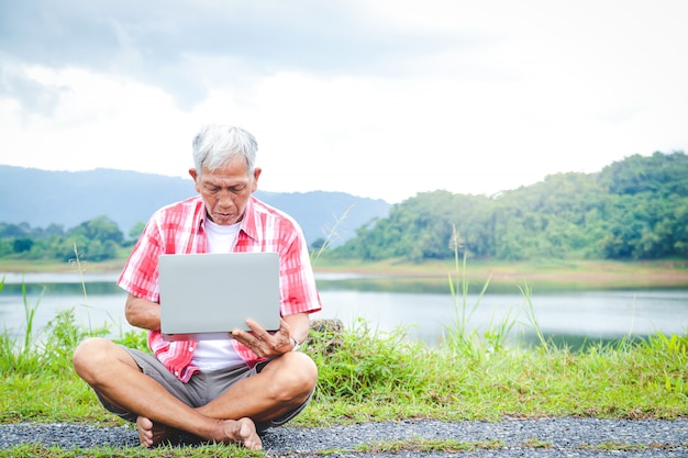 Elderly men asians sit and type in notebooks to work outdoors in the natural park. the concept of a retirement community