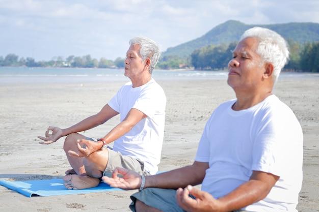 朝の海辺のビーチで年配の男性が運動引退後は幸せな生活を。古いコミュニティとヘルスケアの概念。