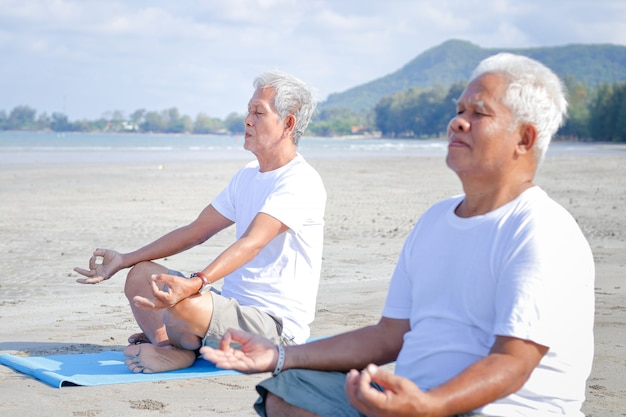 Elderly men exercise at the beach by the sea in the morning have a happy life after retirement. concepts of older communities and health care.
