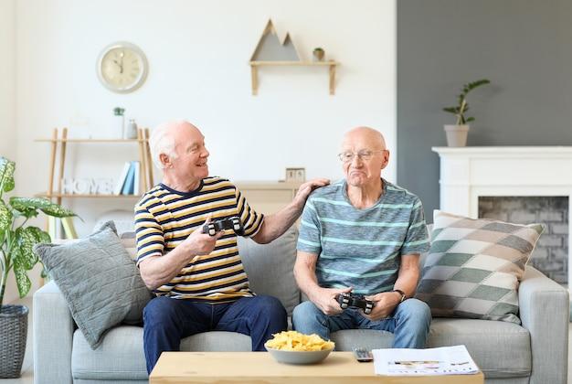 家でビデオゲームをしている年配の男性