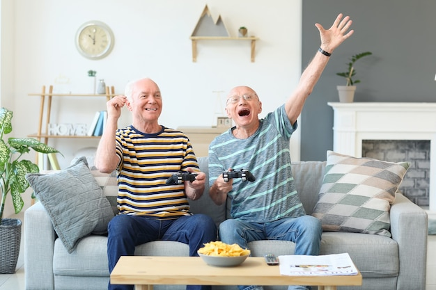 Elderly men playing video games at home