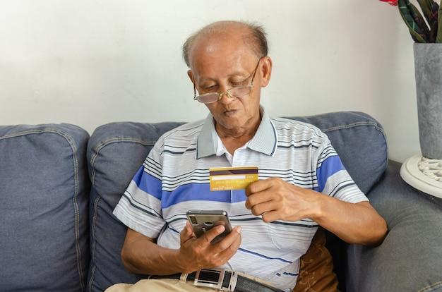 Пожилые мужчины смотрят кредитные карты и мобильные телефоны на диване