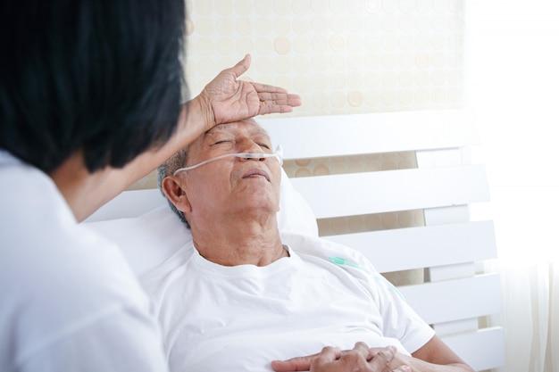 肺疾患や呼吸器疾患のある高齢男性寝室のベッドで世話をする妻がいます。高齢者の健康管理とコロナウイルス感染防止の考え方