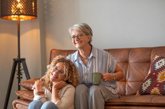 Elderly mother and beautiful adult daughter spending time together at home