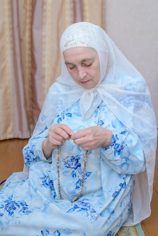 An elderly muslim woman prays