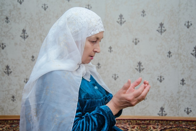 An elderly muslim woman reads prayers
