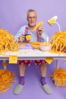Elderly office worker has deadline feels stress from overtime sits at desktop works long hous at project has coffee break surrounded by cut paper
