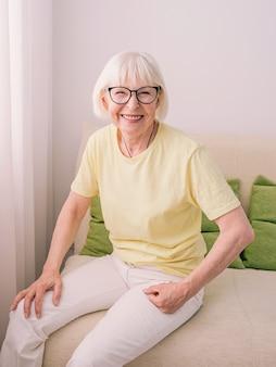 Пожилая старая веселая кавказская стильная женщина с седыми волосами сидит на диване у себя дома