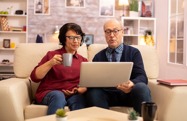 Elderly old couple using modern laptop to chat with their grandson. grandmother and grandfather using modern technology
