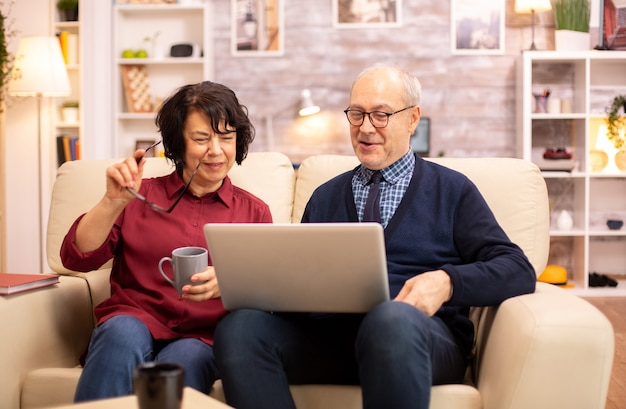 現代のラップトップを使用して孫とチャットする老夫婦。現代の技術を使用している祖母と祖父