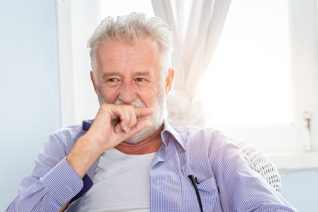 Elderly old man cute hiding smile look shy sitting in room with window.