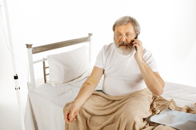Uomo anziano anziano che si sta riprendendo in un letto d'ospedale isolato sul muro bianco. ottenere cura. concetto di sanità e medicina. copyspace.