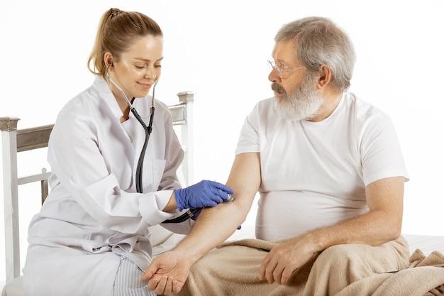 흰 벽에 격리된 편안한 병원 침대에서 회복 중인 노인