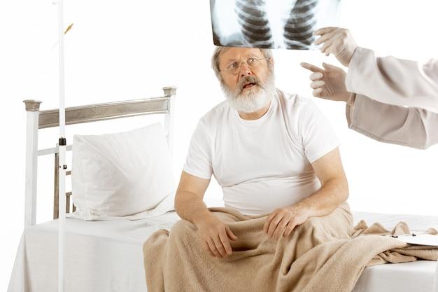 白で隔離の快適な病院のベッドで回復している老人