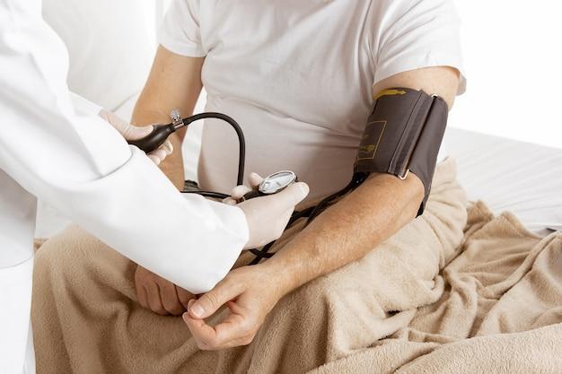 흰 벽에 격리된 병원 침대에서 회복 중인 노인. 관리 및 치료 받기. 의료 및 의학의 개념입니다. 혈압을 측정하는 간호사를 닫습니다. 카피스페이스.