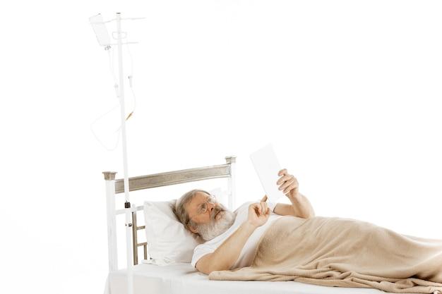 白で隔離された病院のベッドで回復している老人