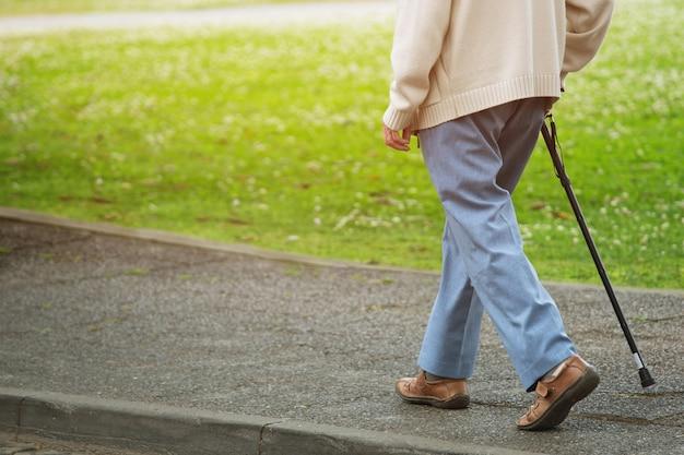 Пожилой старик с тростью стоит на тротуаре пешеходной дорожки, переходя улицу в одиночестве на обочине дороги в общественном парке