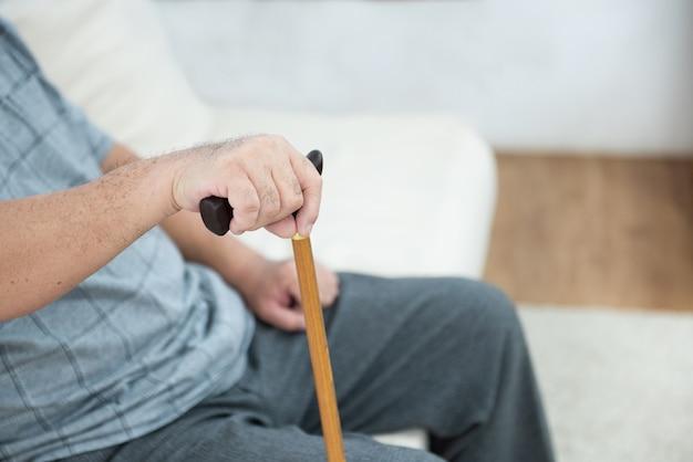 Пожилое старшее усаживание старшего человека, отдыхая его руки на деревянной трости сидя на кресле в живущей комнате в доме после выхода на пенсию.