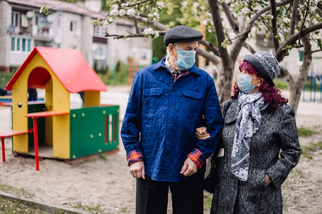 Elderly pair in protective medicine masks outdoors. old people with covid protection on faces in town yard.