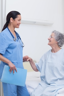 Elderly patient holding the hand of a nurse