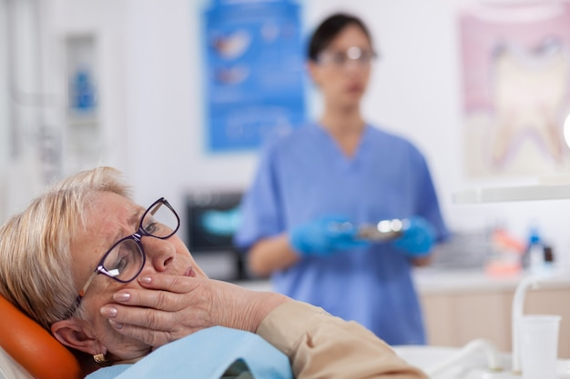 Elderly patient in pain at dentist clinic waiting diagnosis from doctor in medical office