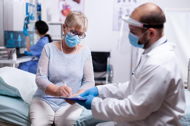 Пациент пожилого возраста подписывает медицинское соглашение о результатах анализов в защитной маске от пандемии коронавируса в больнице